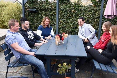 MIDTPUNKT: Hunden Zoe er naturleg midtpunkt for storfamillien. F.v. og rundt bordet med klokka: Papa Kim, Omar, mama Kristin, Osama, Amina og Malin.