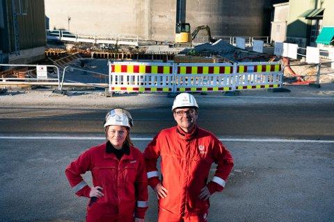 Fabrikksjef Johan Berg og prosessoperatør Madelen Ølmheim gler seg over alt som skjer og skal skje ved Hydro Husnes framover. I bakgrunnen, like ved dei karakteristiske siloane, er grunnarbeidet for eit nytt kompressorbygg i gang.