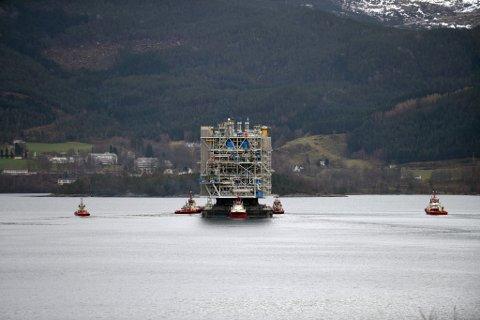 Her flyt plattformoverbygget på ein lekter i Høylandssundet, medan fleire taubåtar kontrollerer den dyrebare lasta. I bakgrunnen kan ein skimta Valen sjukehus.