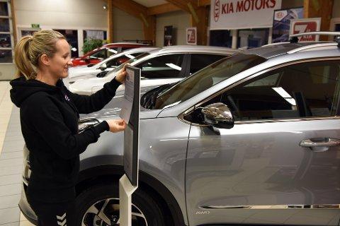 KIA I SKOTET: Lindy Hjelmeland Naterstad rettar på eit faktaark på Kia-sida i S. Rødsten Bilforretning sin bilhall.