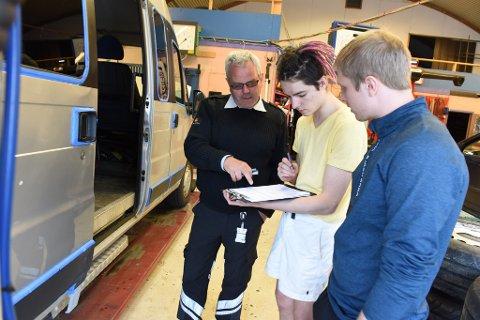 Sveinung Bauge (t.v.) frå Statens vegvesen forklarar russegutane Jonas Ridzevicius og Torstein Myklebust om bilbyråkrati.