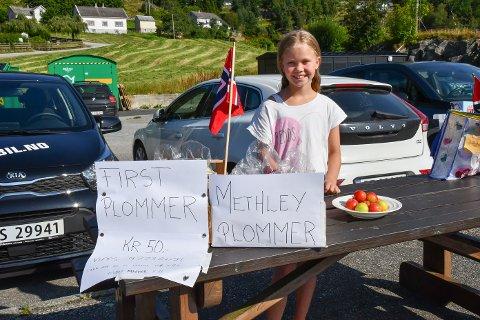 UNG SELJAR: Mathea Askeland (9) har laga seg sin eigen sommarjobb: Ho sel plommer på kaien på Utåker.