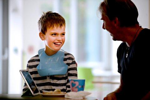 Nettbrettet på bordet inneholder en applikasjon, som er utviklet av Lukas Hopes far, Morten. App-en hjelper Pål Frydenberg og de andre ledsagerne til å forstå multihandikappede Lukas (9) bedre.