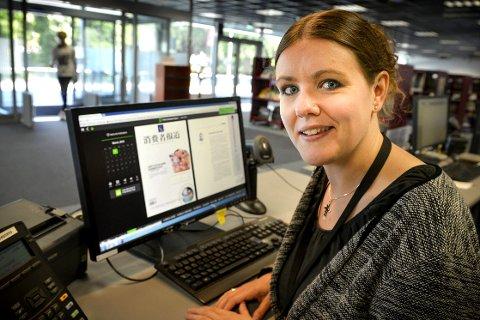 Nyheter fra verden: Elena Linn Beardy ved Kongsberg bibliotek har her funnet en avis fra Kina. Foto: Eigil Kittang Ramstad