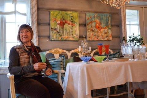 HERSKAPELIG: På veggen henger to malerier av Nenna Steinset Halvorsen. Hun synes omgivelsene er flotte. For eksempel er bordet pyntet med glass fra Jarle og Camilla Knapstad.