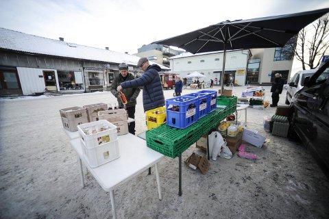 SISTE DAG: Roald Nilsen (t.h). slår av en prat med Håkon Green Leikås ved boden hans på Nytorget i Kongsberg, fredag. Det var Leikaas siste dag som torghandler i Kongsberg.