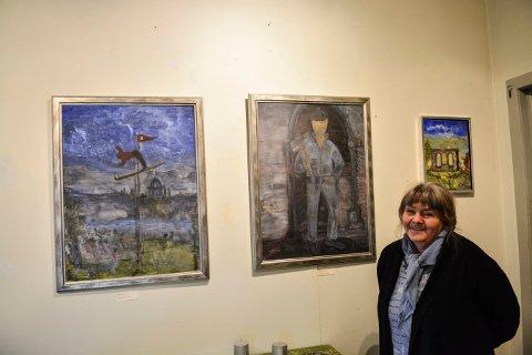 LOKALE MOTIVER: Berith Kjørstad ved tre av sine malerier som er med på utstillingen i Landstadsgate 4.