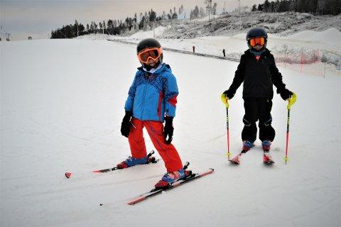 EN GANG TIL: Brødrene Aksel (5) og Joachim (7) Kjellerød hadde tatt turen fra Kragerø for å stå på ski i Kongsberg denne lørdags ettermiddagen. De to har hytte på Rjukan, men der var ikke bakken åpent enda, så da ble turen lagt til Kongsberg Skisenter isteden. –Kan vi ta en runde til?! Spør de to håpefullt. De hadde full fart ned bakken gang på gang, og var tydelig glad for å endelig ha snø under skia igjen.