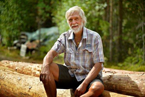 SKOGENS KONGE: Kjell Mogen er leder for Middelalderverkstedet i Rollag, og sitter her på toppen av stokkene som skal bli det nye langhuset.