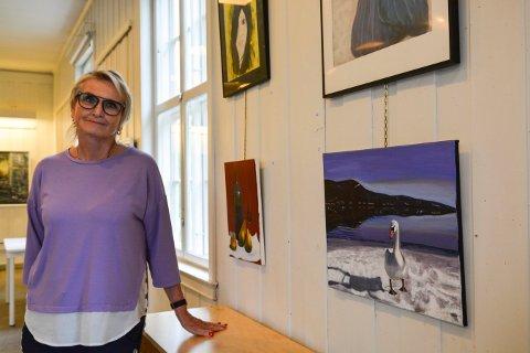 NY KUNST: Leder i Kongsberg malerklubb, Solfrid Konningen Wessel, ønsker velkommen til utstilling de to kommende helgene. Her står hun ved bildene til Mette Heidi Prestegården, som er nykommer i klubben.