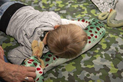 HVILER PÅ SLANGE: Her er det en liten gutt som har lagt seg ned i sanserommet sammen med en tøyslange.