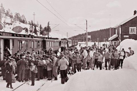 SKIFØRE: Vinteren 1921 var ikke speseilt god for dem som likte snø, is og vinteraktiviteter. Den ene uka etter den andre kom stort sett med «nullføre» og sol fra skyfri himmel. Men i mai kom det kulde og snøbyger. Bildet er antagelig fra 1930-tallet og viser skiturister på Meheia stasjon som venter på å få utlevert skiene fra godsvogna.