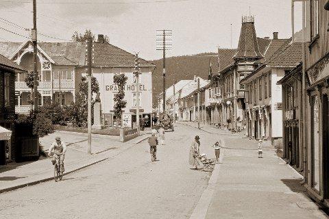STORGATA: Fotografert en fin sommerdag midt på 1920-tallet. Poul Steenstrup har på dette tidspunktet stått foran Grand Hotell i en ti, tolv år eller mer og på ingen måte hindret den beskjedne trafikken. Vi viser et utsnitt av bildet.