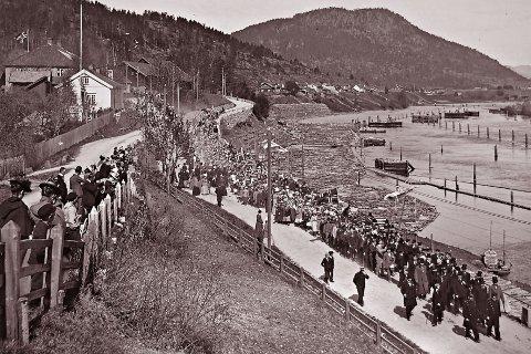 17.MAI: Bildet er antagelig tatt en 17. mai for rundt hundre år siden. Toget er på vei nedover Numedalsveien.
