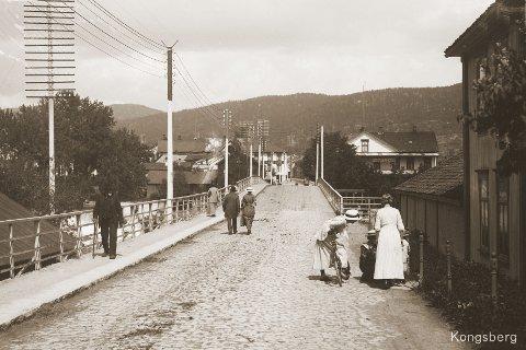 SOMMER: Bildet viser Nybrua sett fra Vestsida en fredelig sommerdag rundt 1914. Både telefon- og strømledninger har, som vi ser, blitt en del av bybildet.