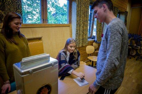 Til urnen: Vibeke Skage og Hanna Louise Ingvaldsen Børrestad kontrollerer at alle prosedyrer er gjort riktig for valget. Her er det Markus Fuglsang Kentsrud som avgir stemme.foto: simen næss hagen