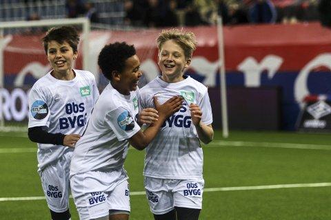 MÅLKONGE: Noah Juel Bache (t.h.) gratuleres av medspillerne sine etter ett av de tre målene han besørget under Drømmekampen, der 33 barn fra hele Norge spilte oppvisningskamp mot to eliteseriespillere.