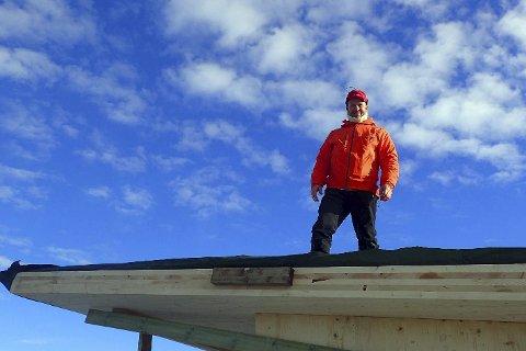 Måke snø: Byggmester Øystein Henriksen måtte opp på taket å måke snø før sluttspurten med å få ferdig rastebua på Gjevlekollen kunne settes inn.