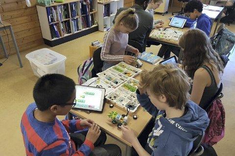 SAMARBEID: Sofija (11), Dave (11), Christopher (11) og Kaja (12) i dyp konsentrasjon over Lego-settene, der oppdraget var å lage sin egen Lego-robot, og få den til å gå framover, bakover og til siden.