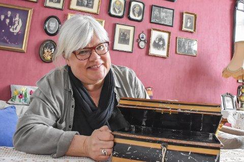 Skrinet: Tone B. Bergflødt med skrinet etter farfaren som har en hovedrolle i boka hun lanserer 3. mai. På veggen bak henne henger flere familiebilder, blant annet av farfaren som har hatt en stor innvirkning på Tones liv, både på godt og vondt.