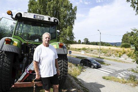 PROVOSERT: Utvidelsen av Jensvollveien og den midlertidige kryssløsningen gjør at epleprodusent Knut Eilert Sørnes frykter trærne i bakgrunn vil falle, og at han må kutte ned epletrær.FOTO: PÅL A. NÆSS