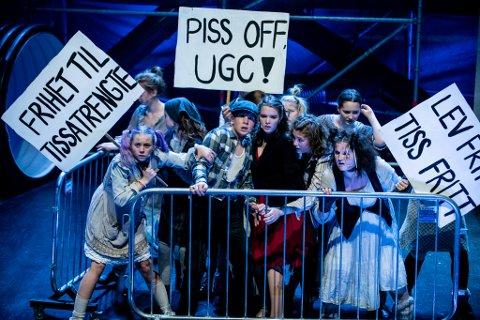 TISSETRENGTE: Henrik Sarre-Hammer og Juni Marie Løveid Mølster (i front) spiller to av hovedrollene i musikalen «Urinetown». Hva UGC står for? Urine Good Company ...!
