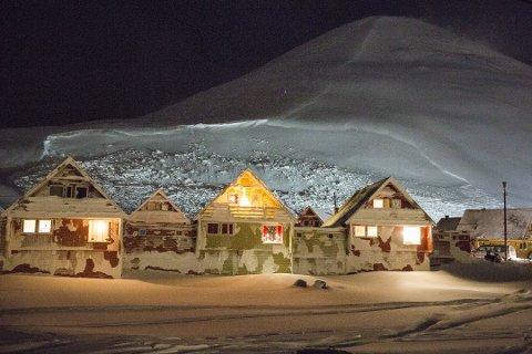 Husene i Nybyen i Longyearbyen er evakuert etter at det gikk et stort snøras. Det er fare for nye ras fra fjellet i bakgrunnen som heter Sukkertoppen.