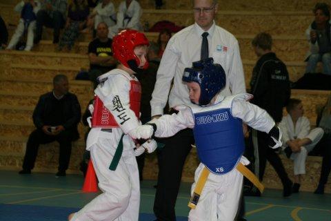 Leander Karlsen og Simon Pleym Jonassen går teakwondokamp i Vaagar Idrettspark.Dommer Stig Arne Gundersen følger med.