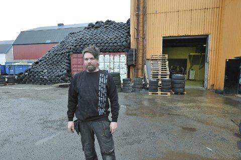 Dekkhotellet: Morten Hansen selger vel 6000 nye dekk til bileierne i Lofoten hvert år, og det vises på bruktdekklageret bak han. I industrihallen til høyre bygger han nå ut dekkhotellet for å tilby helårslagring til langt flere bilkunder. Foto: Knut Johansen