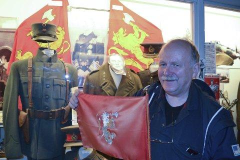 Bordflagg: William Hakvaag viser frem bordflagget til kongen. I bakgrunnen Kronprinsflagget og Kongeflagget.