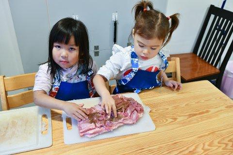 Ruth og Grace sikrer at krydderblandingen masseres godt inn i sidekjøttet på julesylta.