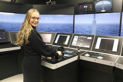 FULL FART: Fylkesråd for utdanning Sandra Tønne til rors ved en av skipsbrosimulatorene ved den nye skolen.