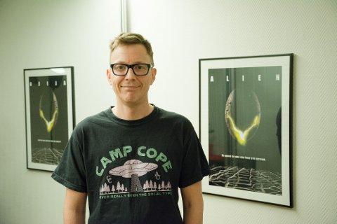 UTENOMJORDISK POPKULTUR: For 30 år så Tom Nedrebø (46) noe uforklarlig på Gravdal. Hjemme i Storfjorden har han tilfeldigvis filmplakaten til Alien hengende på veggen. Den flyvende tallerkenen på t-skjorta? Heelt tilfeldig det og! Camp Cope er et australsk band som han liker.