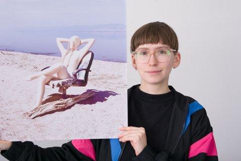 DØDE FISK: Tine Surel Lange (31) flyttet til Fredvang etter å ha sett sandstranda der. På bildet hun holder, sitter hun på en giftig strand i USA, der bredden består av bein fra millioner av døde fisk.