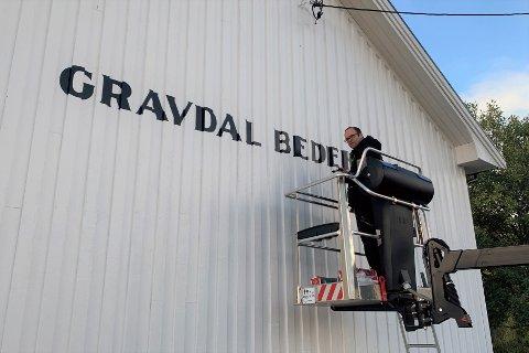 Skiltmaler Kristian O. Gundersen malte skilt på veggen på Gravdal bedehus sist helg.
