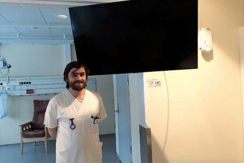 Helsefagarbeider Kristoffer Mauno ved medisinsk avdeling på Nordlandssykehuset Lofoten viser fram TV-apparatet som er kjøpt inn med midler fra LHL Stamsund.