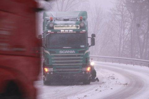 VANLIG: Scener som dette har blitt vanlig langs vinterveiene gjennom Lybgdal. Her legger en dansk sjåfør på kjetting midt i Lenebakken.