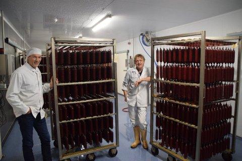 PØLSER: Her henger rødvinspølsene til tørk. Daglig leder Rune Svindland (til venstre) og produksjonsleder Olav Terje Eriksen. Foto: Erik Thime