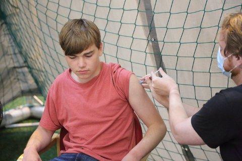 VAKSINE: Her setter Per Inge Høyland sprøyten, og Adrian Seglem Andalsvik får med det første dose av Pfizer-vaksinen.