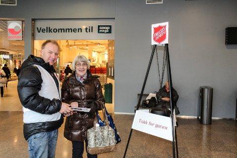 SNART JUL: Julegryta til Frelsesarmeen er på plass i Amfi Moss. Anne-Mari Nessjøen puttet penger i gryta og fikk takk fra frivillig grytevakt Knut Peder Abrahamsen.
