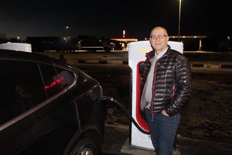 FORNØYD: Hans Petter Karlsen lader sin Tesla. Han er fornøyd med ladestasjonen.