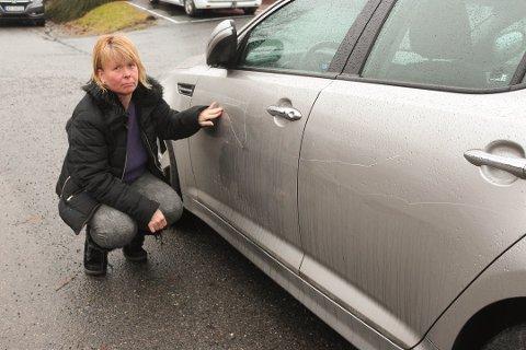 TRIST: Wenche Enersen er trist og lei for at noen har påført bilen hennes stygge lakkskader ved å ripe langs hele siden på bilen. - Jeg forstår ikke vitsen med slik hærverk, sier hun.