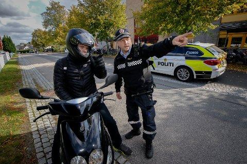 KONTROLL: Politiførstebetjent Knut Arne Berger stoppet en mopedist utenfor Malakoff videregående skole og forklarte at det kun er lov å holde gangfart når man kjører i gatetunet. Nå ber han foreldre om å vise ansvar og ta en prat med ungdommen som ferdes på tohjulinger.