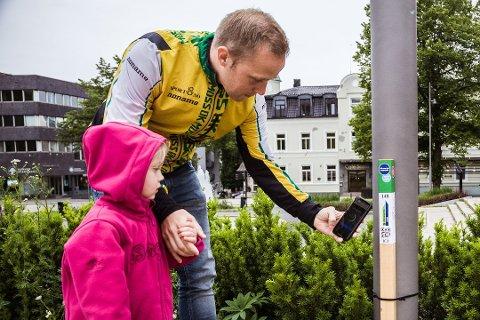 POPULÆRT: I fjor var det stolpejakt-feber i Moss. Her fulgte Ella Rytter Jakobsen nøye med mens pappa Erik Rytter Jakobsen scannet QR-koden på stolpen i Moss sentrum.