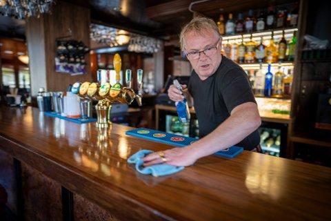 Tidligere FrP politiker Per Sandberg rengjør bardisken før åpningen av puben Grand Bar i Halden.