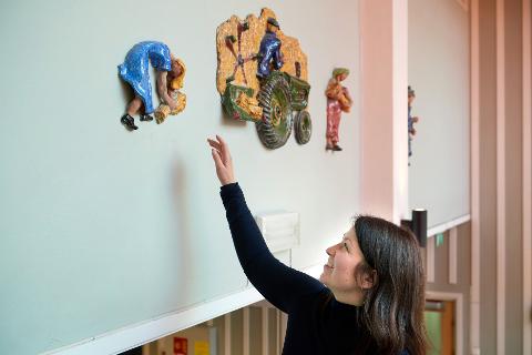 KUNSTSKATTER: Namsos kommune skal nå skaffe seg en oversikt over kunsten de eier. – Kommunen har jo store verdier i form av kunst i sitt eie, men vi har ingen helhetlig oversikt, sier prosjektkoordinator Gudrun Flatebø, som her inspiserer et verk av Alvhild Finsberg, hvor deler henger i Namsos Samfunnshus, mens resten ligger lagret i magasin.