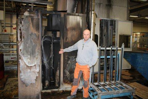 HER STARTET BRANNEN: Daglig leder ved Bindalsbruket, Jan Håvard Brevik, står ved skapet der brannen startet tirsdag ettermiddag. – Jeg oppdaget lukt og røykdamp, og ikke lenge etter stod det flammer ut av dette skapet.