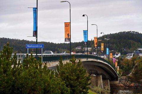 SLUTT PÅ FLAGG: I flere år har lyktestolpene på Namsosbrua vært dekorert med flagg som ønsket velkommen til byen. Nå har fylkeskommunen sagt at det er det slutt på en gang for alle. Bildet er fra sommeren 2017.