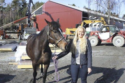 Gleder seg: Rideskoleansvarlig Julie Fogge (med hesten Lykke) håper det nye ridehuset på Lofsrud blir ferdig i løpet av sommeren.  Foto: Arne Vidar Jenssen