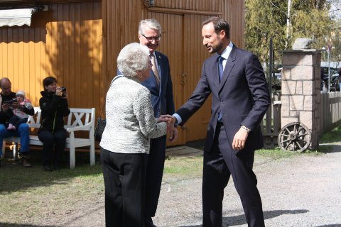 Kronprins Haakon hilser på frivillig Tordis Nilsen.